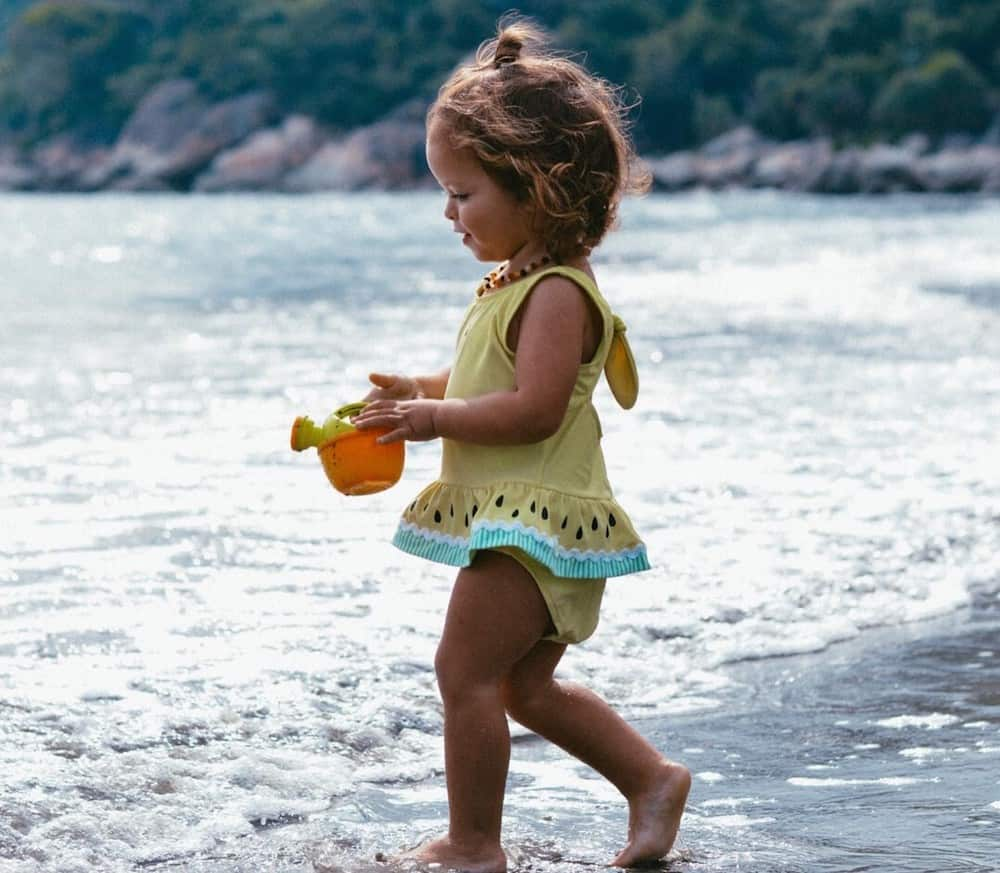 Toddler in swimsuit on the beach