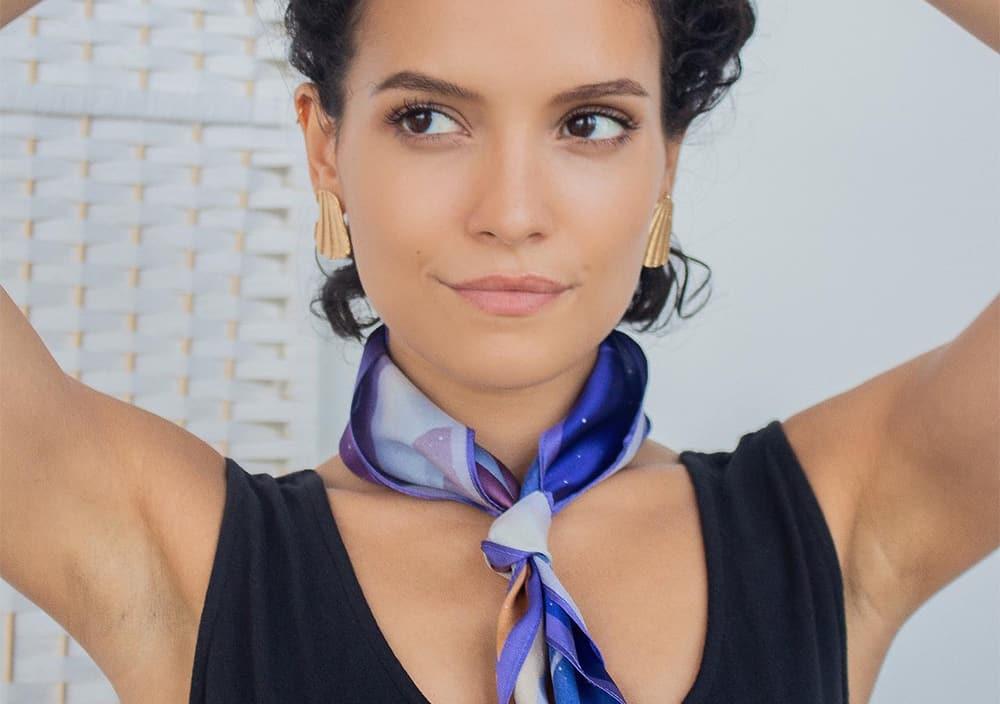 Model wearing purple neck scarf and gold earrings