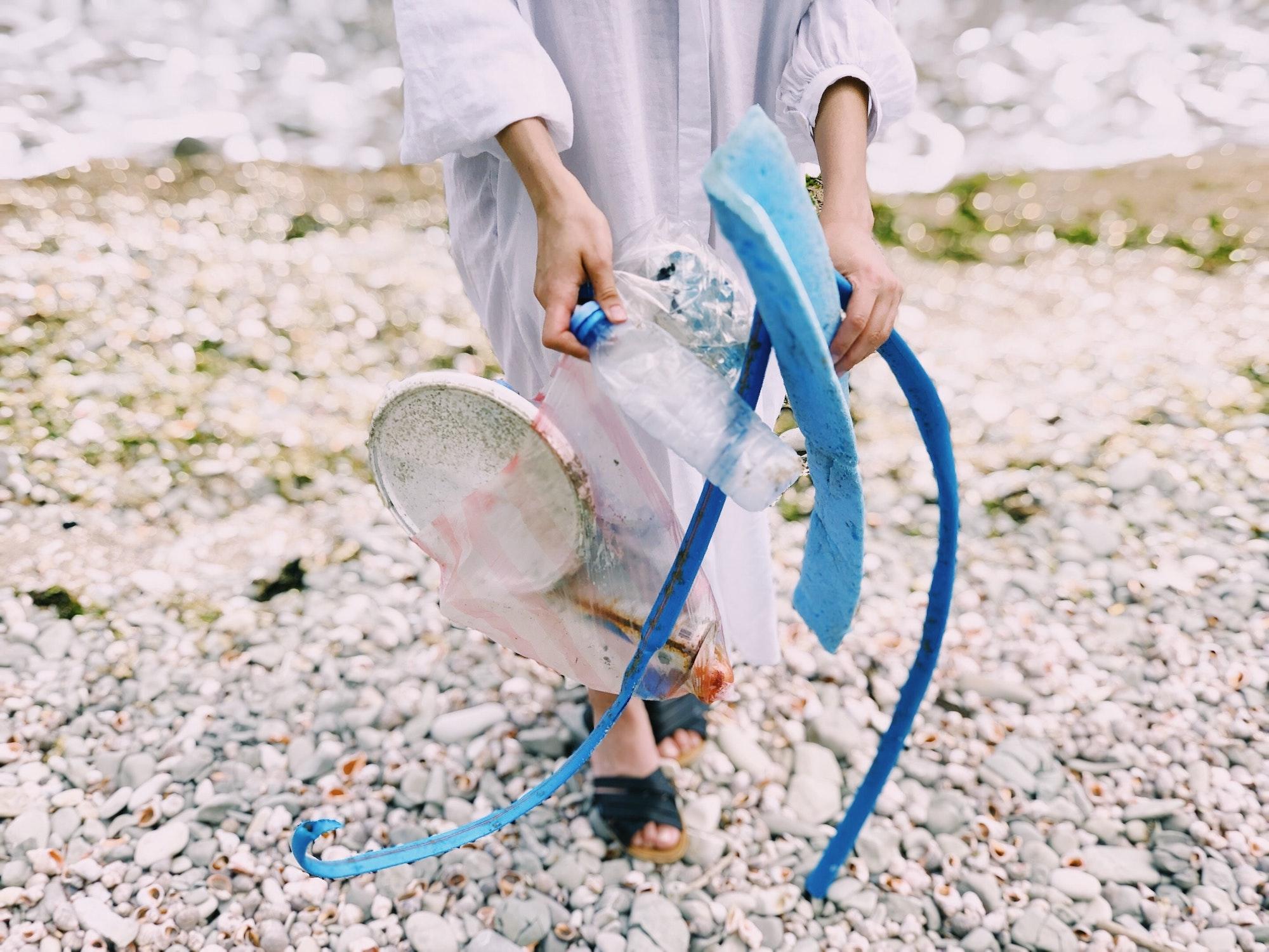 Girl holding trash on a beach