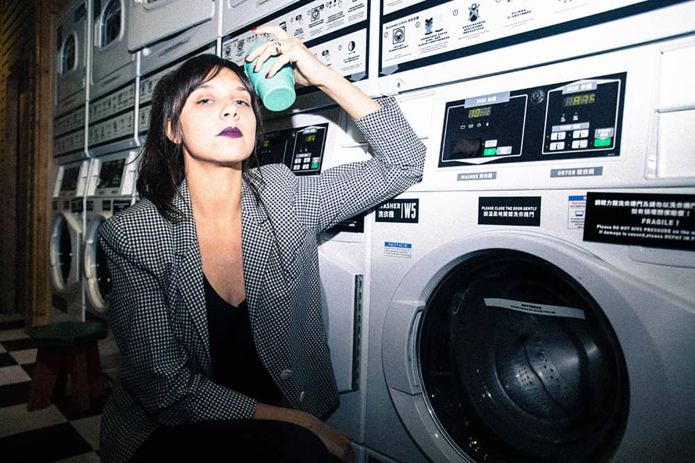 a girl holding a cup leaning against a washing machine