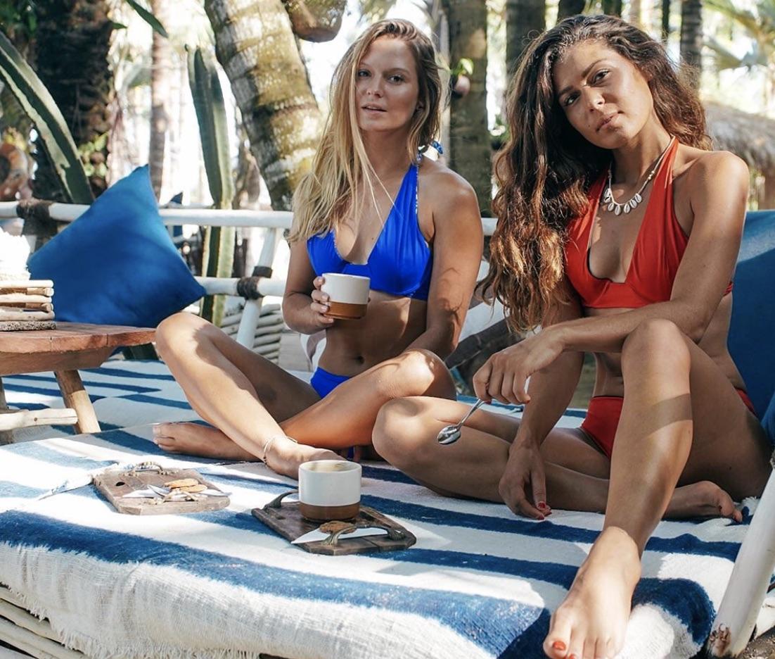 Two girls wearing bikinis drinking coffee