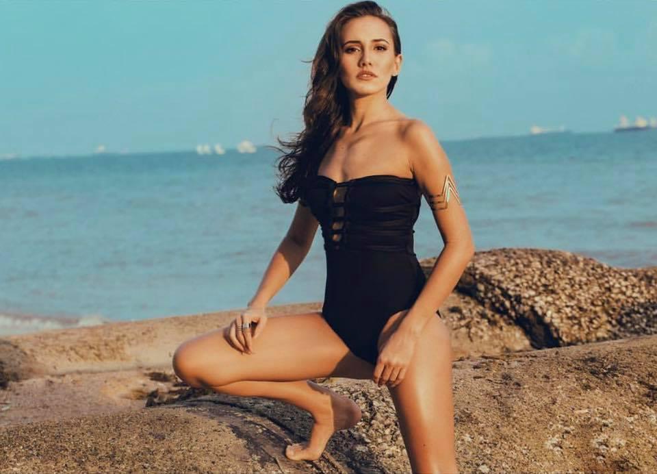 Woman in a black swimsuit near the sea