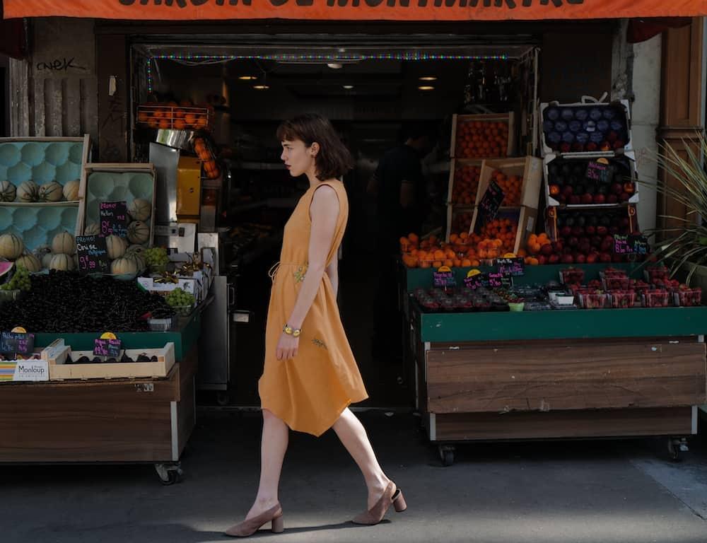 Girl walking in front of vegetables